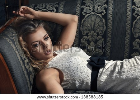 Young beautiful luxurious woman lying on a vintage couch - stock photo