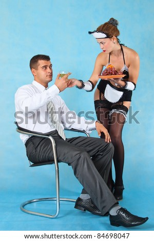 Young beautiful maid serves her master - stock photo