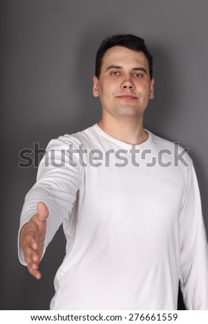 Young beautiful man holds out his hand for handshake in grey studio - stock photo