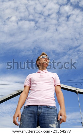 Young beautiful man model standing under the cloudy sky. Blue cloudy sky background.