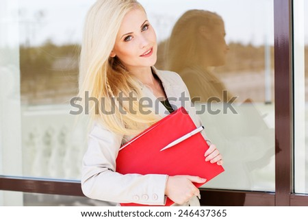 Young beautiful manager girl is holding pen and red folder over window