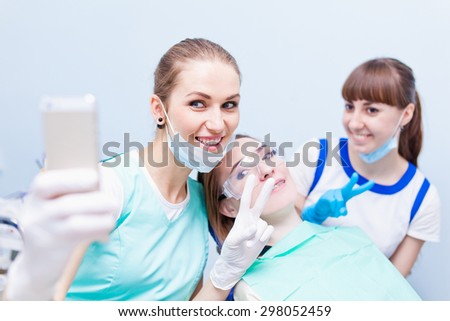 Young beautiful medical doctors dentist hygienist orthodontist and her assistant making selfie with happy patient with peace sign smiling after successful treatment - stock photo