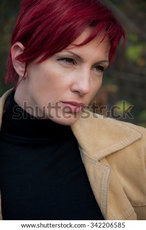 young beautiful melancholic woman with short red hair shallow depth of field - stock photo