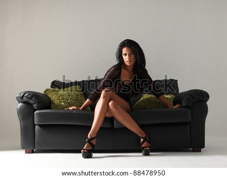 Young beautiful mixed race fashion model with long legs and stilettos wearing short sexy black skirt and lace top sitting cross legged on leather sofa with green cushions. - stock photo