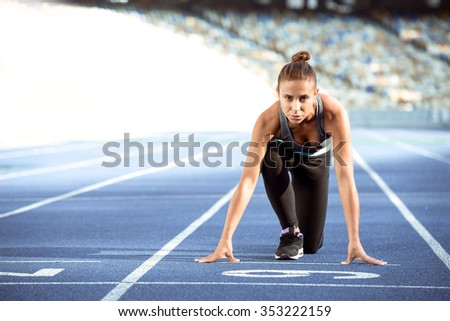 Young beautiful mixed race sportswoman is ready to run on racetrack . Fit woman is at large nice modern stadium - stock photo