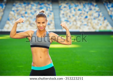 Young beautiful mixed race sportswoman outdoors. Fit woman is at large nice modern stadium. Athlete showing her biceps and smiling - stock photo