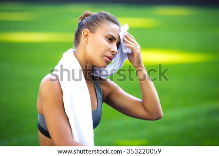 Young beautiful mixed race sportswoman resting outdoors. Fit woman is at large nice modern stadium. Tired woman wiping sweat with towel - stock photo