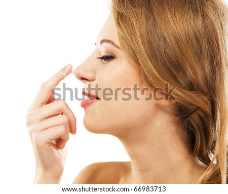 Young beautiful model applying face cream, white background - stock photo
