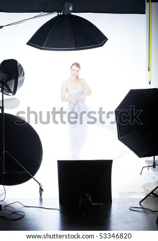 Young beautiful model posing in professionally equipped studio, waving by light fabric over white - making high key