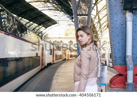 young beautiful modern businesswoman waiting for the train at the railway station. pretty young well-dressed blonde woman looking for her needed railway platform