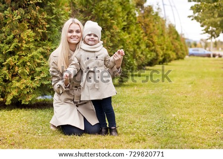 Young beautiful mom and her daughter wearing beige raincoats with umbrellas, autumn fashion style, fall family same look, clothing for parent and child.