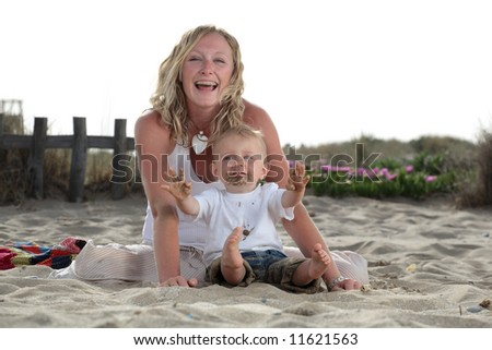 young beautiful mommy playing with her baby son on the beach - stock photo