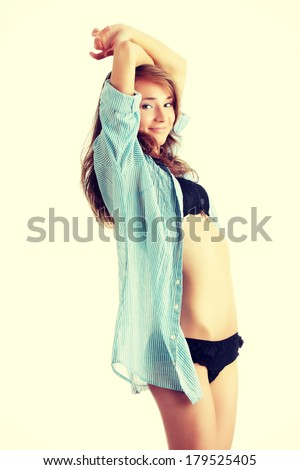 Young beautiful morning woman in big shirt and underwear  stretching - stock photo