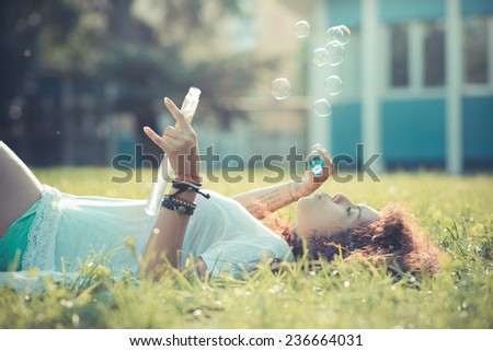 young beautiful moroccan curly woman blowing bubbles at the park - stock photo