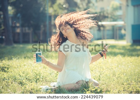 young beautiful moroccan curly woman listening music with smartphone at the park - stock photo