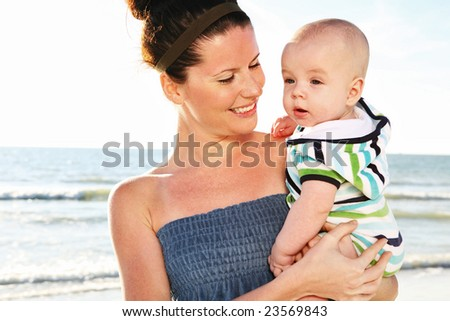 Young beautiful mother and child on sunny beach.