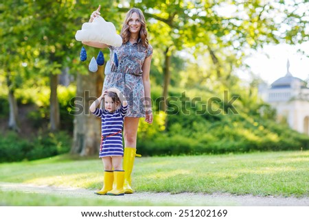 Young beautiful mother and her adorable daughter in yellow rubber boots, family look, in summer park playing with rain drops toy - stock photo