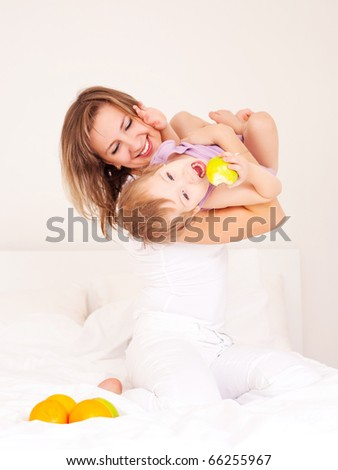 young beautiful mother and her baby on the bed at home (focus on the child) - stock photo