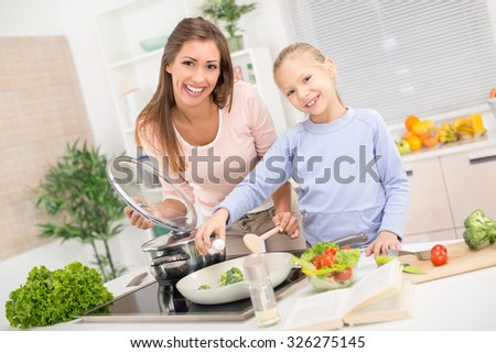 Young beautiful mother and her cute daughter cooking healthy meal in the kitchen. - stock photo