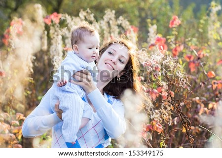 Young beautiful mother and her little baby playing in a sunny autumn park - stock photo