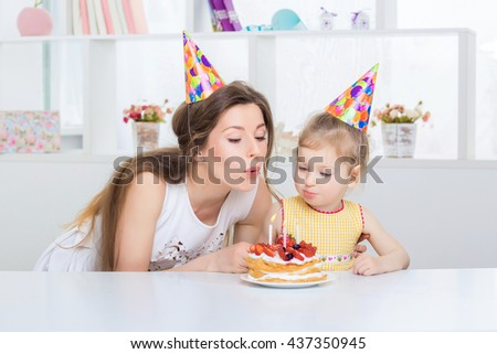 young beautiful mother and her little daughter are celebrating a birthday. on the table is a cake with candles. mom and daughter are blowing on candles - stock photo