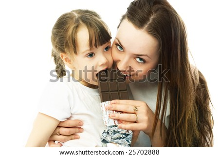 young beautiful mother and her little daughter eating chocolate - stock photo