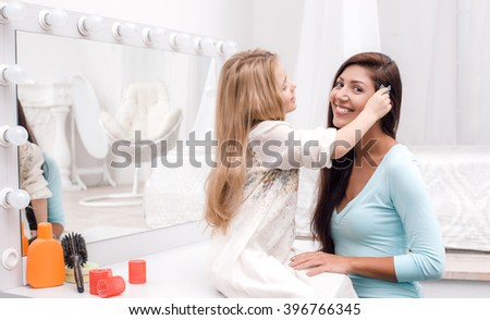 Young beautiful mother and little daughter while applying makeup. Nice cozy bedroom. Daughter helping mother to make hair done - stock photo