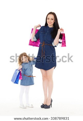 Young beautiful mother and sweet little daughter standing with shopping bags on a white background. Shopping family. - stock photo