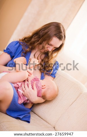 Young beautiful mother breastfeeding her 8 months old daughter - stock photo