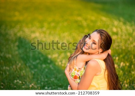 Young beautiful mother embraces her child (daughter) - outdoor in nature - stock photo