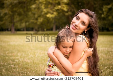 Young beautiful mother embraces her child (daughter) - outdoor in nature