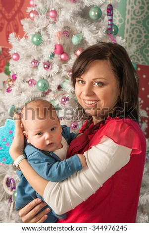 Young beautiful mother holding a two-month old baby near Christmas tree
