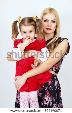 Young beautiful mother holding daughter - stock photo