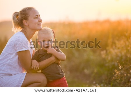 Young beautiful mother hugging her little toddler son on a sunset in a wild flowers field. Happy woman with her baby boy on a summer sunny day. Family walking on the meadow. - stock photo