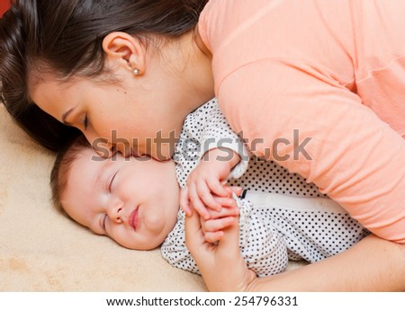 Young beautiful mother kissing her calmly sleeping baby. - stock photo