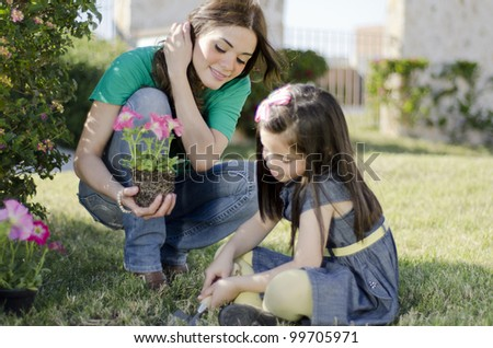 Young beautiful mother planting some flowers with her daughter