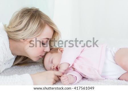 Young beautiful mother puts her baby daughter to sleep. motherhood concept, love and care. - stock photo