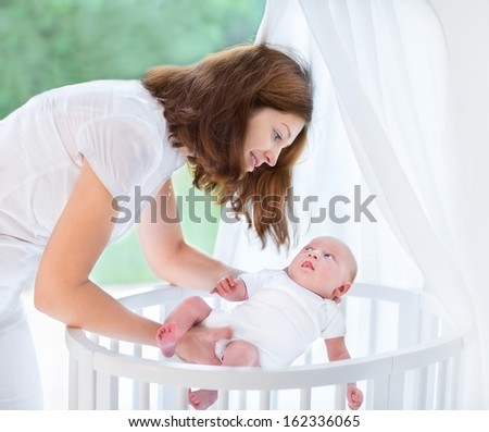 Young beautiful mother putting her newborn baby into a white round crib with canopy next to a big window - stock photo
