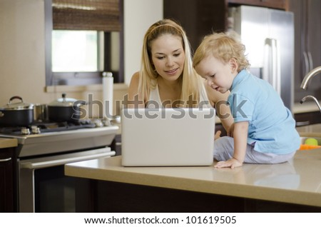 Young beautiful mother showing something to her son in her laptop