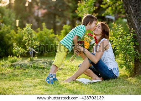 Young beautiful mother, sitting in a garden, little boy, her son, bringing gerbera flowers and present for her, mothers day surprise - stock photo