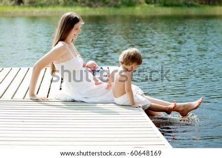 young beautiful mother spending time with her children outdoors - stock photo