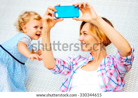 Young beautiful mother takes selfie with her daughter - stock photo