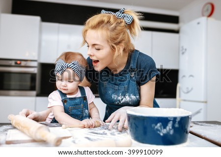 young beautiful mother teaches daughter prepare dough in the kitchen with fun