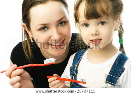 young beautiful mother teaching her little daughter brushing teeth - stock photo