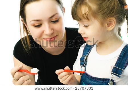 young beautiful mother teaching her little daughter brushing teeth