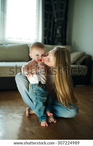 young beautiful mother with baby sitting on the floor - stock photo