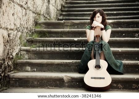 Young beautiful music performer caressing her guitar - stock photo