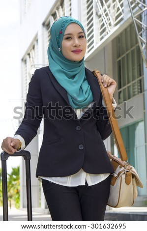 Young Beautiful Muslim business woman holding handbag and smile  - stock photo
