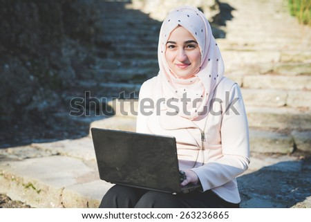 young beautiful muslim woman at the park in spring using notebook connected online working  - stock photo