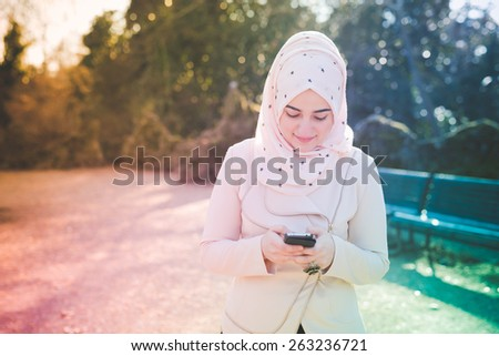 young beautiful muslim woman at the park in spring using smartphone connected online wireless - stock photo